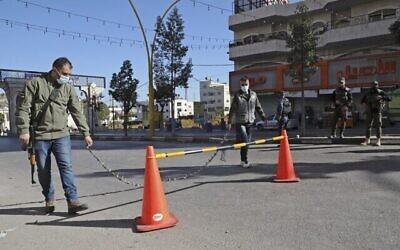 قوات الامن الفلسطينية تغلق المدخل الشمالي الرئيسي لفرض حظر التجول وسط جائحة كوفيد-19 في مدينة الخليل بالضفة الغربية، 11 ديسمبر، 2020. (HAZEM BADER / AFP)