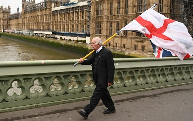 31 يناير 2020 رجل يحمل علم سانت جورج ماشيا على جسر وستمنستر بالقرب من مجلس النواب في لندن Photo by Glyn KIRK / AFP