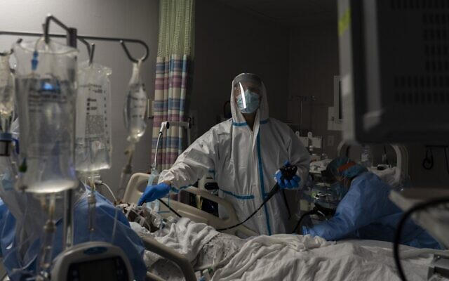 """طبيب يفحص مريض باستخدام منظار داخلي في وحدة العناية المركزة لكوفيد-19 في مركز """"يونايتد ميموريال"""" الطبي في هيوستن، تكساس، 29 ديسمبر 2020 (Go Nakamura/Getty Images/AFP)"""