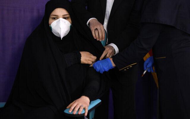 """طيبة مخبر تتلقى لقاح فيروس كورونا """"كوريفان"""" الذي تنتجه شركة Shifa Pharmed، وهي جزء من شركة أدوية تابعة للدولة، في حفل أقيم في طهران، إيران، 29 ديسمبر 2020 (AP Photo / Aref Taherkenareh)"""