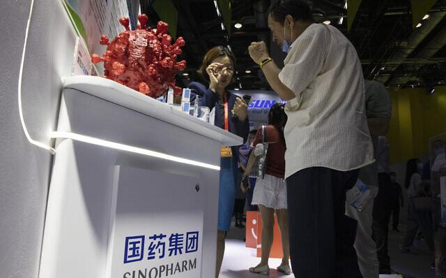 """مسوّقة تتحدث عن لقاح كوفيد-19 الذي تنتجه شركة CNBG التابعة لشركة """"سينوفارم"""" الصينية خلال معرض تجاري في بكين، 6 سبتمبر 2020 (Ng Han Guan / AP)"""