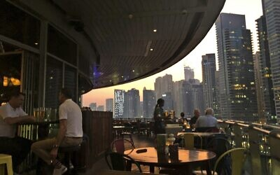 اشخاص يستمتعون بتناول المشروبات الكحولية في مطعم يطل على منطقة المارينا في دبي، الإمارات العربية المتحدة، 23 أكتوبر 2019 (AP Photo / Kamran Jebreili)