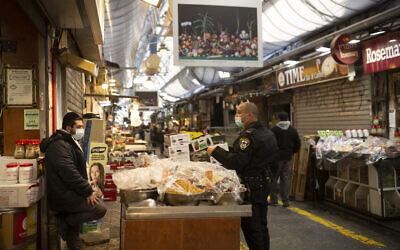رجل شرطة يتحدث مع بائع في سوق محانيه يهودا في القدس، خلال الإغلاق الوطني الثالث لإسرائيل للحد من انتشار فيروس كورونا، 28 ديسمبر 2020 (AP Photo / Maya Alleruzzo)