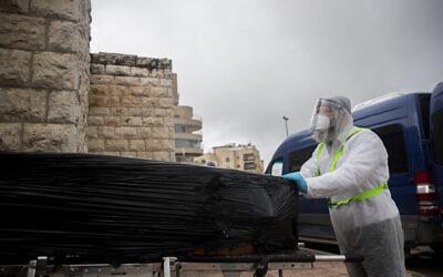 عمال في جمعية الدفن 'حيفرا كاديشا' يرتدون زيا واقيا خلال نقلهم لجثة مريض توفي جراء تعقيدات ناجمة عن فيروس كورونا في دار الدفن 'شمغار' في القدس، 1 أبريل 2020 (Yonatan Sindel/Flash90)