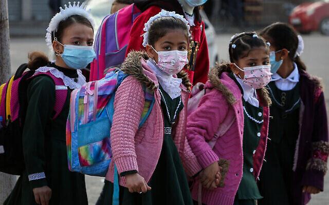 """طلاب فلسطينيون في مدرسة تاربعة لـ """"أونروا"""" يرتدون كمامات وسط تفشي فيروس كورونا، في رفح جنوب قطاع غزة، 25 نوفمبر، 2020. (Abed Rahim Khatib / Flash90)"""