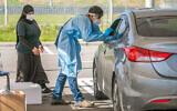عاملون في مجال الرعاية الصحية يأخذون عينات في محطة فحوصات كورونا متنقلة في اللد، 1 ديسمبر، 2020. (Yossi Aloni / Flash90)