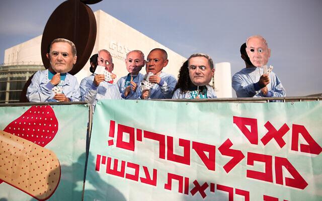 نشطاء إسرائيليون يرتدون أقنعة لرئيس الوزراء بنيامين نتنياهو، وزير الدفاع بيني غانتس ووزير المالية يسرائيل كاتس أثناء احتجاجهم ضد الحكومة، في ساحة هبيمة في تل أبيب، 2 ديسمبر 2020 (Miriam Alster / Flash90)