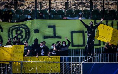 أعضاء مجموعة لا فاميليا يحتجون على نية مالك بيتار موشيه حوغيغ بيع نسبة من المجموعة لأحد أفراد العائلة المالكة الإماراتية ، في ملعب تدريب نادي بيتار القدس بالقدس، 4 ديسمبر، 2020. (Flash90)