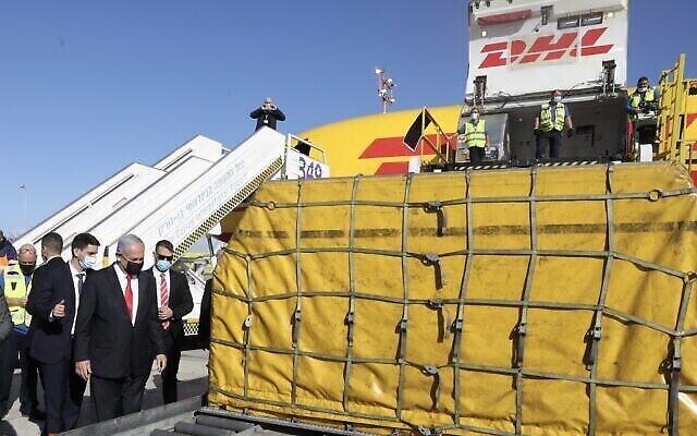 """رئيس الوزراء بنيامين نتنياهو ووزير الصحة يولي إدلشتين يحضران وصول طائرة شحن تنقل الدفعة الأولى من لقاحات """"فايزر"""" إلى مطار بن غوريون، 9 ديسمبر 2020 (Marc Israel Sellem / Pool)"""