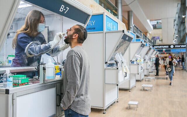 عاملة مختبر تجمع عينات مسحة من الأنف لـتشخيص كوفيد-19 في مختبر كورونا بمطار بن غوريون الدولي، 14 ديسمبر، 2020. (Yossi Aloni / Flash90)