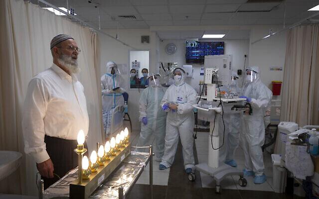 العاملون والمرضى في المركز الطبي شعاري تسيديك يشعلون الشموع  بمناسبة عيد الأنموار (حانوكاه) في قسم كورونا بالمستشفى في القدس، 17 ديسمبر، 2020. (Olivier Fitoussi / Flash90)