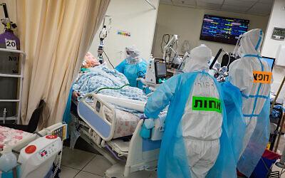 أطباء وممرضين يرتدون ملابس واقية اثناء العمل في جناح فيروس كورونا في المركز الطبي شعاري تسيديك في القدس، 17 ديسمبر 2020 (Olivier Fitoussi / Flash90)