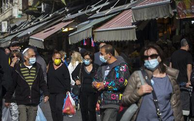 أشخاص يتسوقون في سوق محانيه يهودا في القدس، 21 ديسمبر، 2020. (Olivier Fitoussi / Flash90)