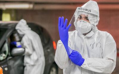 عاملون في مجال الرعاية الصحية يأخذون عينات اختبار فيروس كورونا لإسرائيليين في موديعين، 24 ديسمبر 2020 (Yossi Aloni / Flash90)