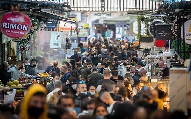 متسوقون يرتدون الكمامات في سوق محانيه يهودا في القدس، 25 ديسمبر، 2020. (Yonatan Sindel/Flash90)