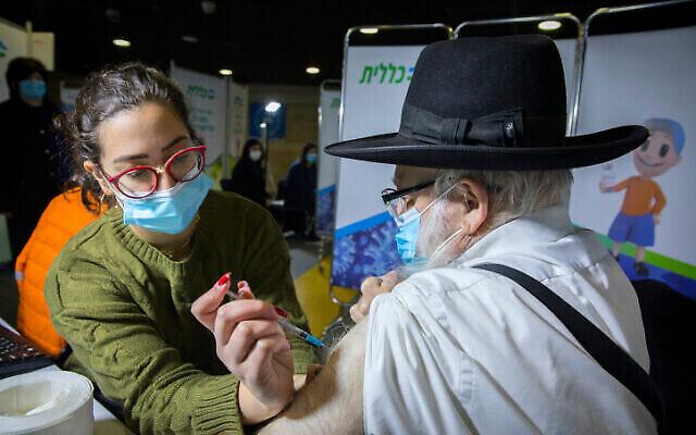 رجل حريدي يتلقى لقاح كوفيد -19، في مركز التطعيم تابع لصندوق المرضى كلاليت في القدس، 29 ديسمبر، 2020. (Olivier Fitoussi / Flash90)