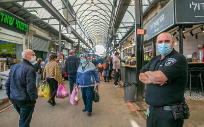 إسرائيليون يتسوقون في سوق في الرملة، وسط إسرائيل، المغلق جزئيا بسبب قيود فيروس كورونا، 23 ديسمبر، 2020. (Yossi Aloni / Flash90)