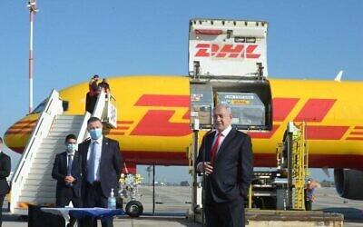 رئيس الوزراء بنيامين نتنياهو يقف أمام الطائرة التي نقلت الجرعات الأولى من لقاحات شركة فايزر المضادة لكورونا، 9 ديسمبر، 2020.  (Marc Israel Sellem/POOL)