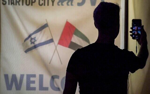 عضو في وفد من قطاع الهايتك الاسرائيلي يستخدم هاتفه في مكالمة فيديو في اجتماع مسائي مع نظرائه الاماراتيين في دبي، 25 أكتوبر، 2020. (Karim SAHIB / AFP)