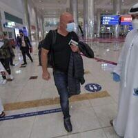 توضيحية: رجل إسرائيلي يسير أمام طاقم إماراتي بعد عبور مراقبة جوازات السفر لدى وصوله من تل أبيب في مطار دبي في الإمارات، 26 نوفمبر، 2020. (Karim Sahib / AFP)