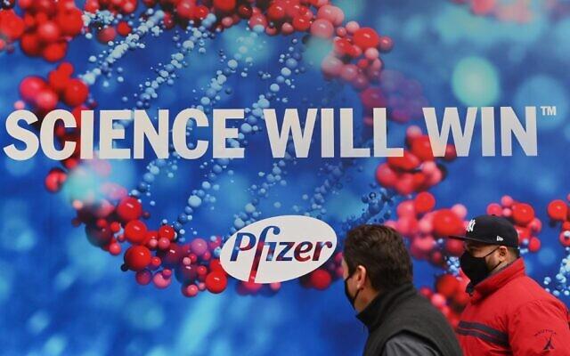 أشخاص يرتدون أقنعة واقية يمرون أمام مقر شركة فايزر، في مدينة نيويورك، 9 ديسمبر 2020 (Angela Weiss / AFP)