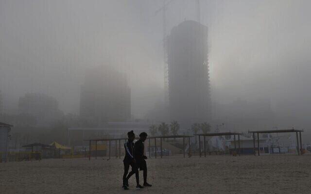 شخصان يسيران على الشاطئ في وقت مبكر من يوم 6 يناير 2021، في مدينة نتانيا الساحلية وسط ضباب صباحي كثيف في الأسبوع الأول من العام الجديد. (JACK GUEZ / AFP)