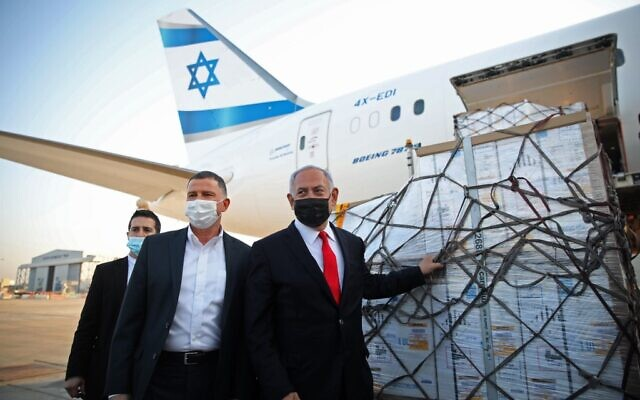 رئيس الوزراء الإسرائيلي بنيامين نتنياهو (يمين) ووزير الصحة يولي إدلشتين (وسط) يحضران مراسم وصول طائرة تحمل شحنة لقاح مضاد لفيروس كورونا من شركة فايزر/بيونتك، في مطار بن غوريون بالقرب من مدينة تل أبيب، 10 يناير 2021 (Motti MILLROD / POOL / AFP)