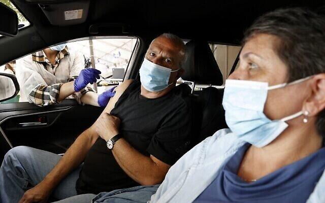 مواطن مسن يتلقى الجرعة الثانية من لقاح فايزر المضاد لكوفيد-19 في مركز التطعيم الخاص بصندوق المرضى مكابي للخدمات الصحية في مدينة حيفا الساحلية بشمال البلاد، 11 يناير، 2021. (JACK GUEZ / AFP)