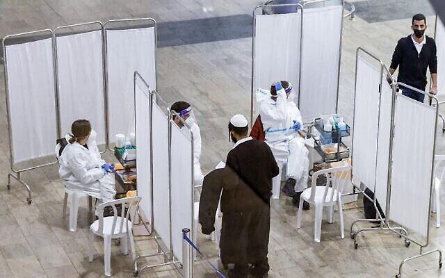 مسافر يتوجه إلى عامل طبي للخضوع لفحص كوفيد-19 عند وصوله إلى مركز الفحص السلايد في مطار بن غوريون الدولي القريب من تل أبيب، 24 يناير، 2021.  (JACK GUEZ / AFP)