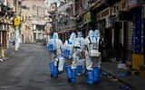 عاملون صحيون يرتدون معدات واقية يستعدون لرش مطهر في منطقة محظورة في منطقة هوانغبو بشانغهاي، بعد إجلاء السكان في أعقاب اكتشاف عدد قليل من حالات الإصابة بفيروس كورونا في الحي، 27 يناير 2021 (STR / AFP)