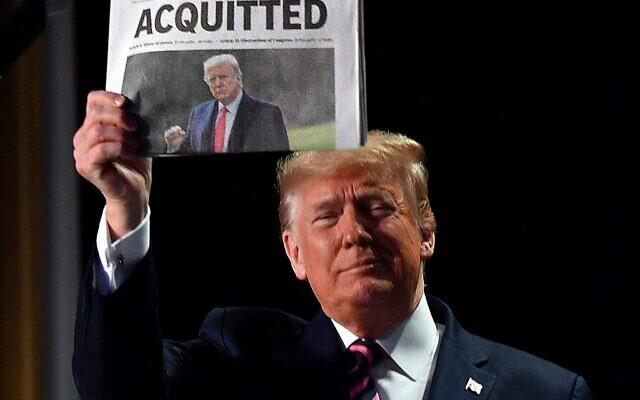 """صورة ملف التقطت في 6 فبراير 2020، يرفع فيها الرئيس الأمريكي دونالد ترامب صحيفة تحمل عنوان """"براءة""""، في واشنطن العاصمة (Nicholas Kamm / AFP)"""