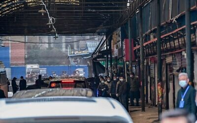 سيارات تنقل أعضاء فريق منظمة الصحة العالمية، الذين يحققون في مصدر فيروس كورونا، تصل إلى سوق هوانان للمأكولات البحرية المغلق في ووهان، مقاطعة هوبي بوسط الصين، 31 يناير 2021 (Hector RETAMAL/AFP)