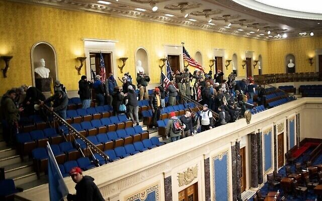 WASHINGTON, DC - JANUARY 06: A pro-Trump mob gathers inside the Senate chamber in the U.S. Capitol after groups stormed the building on January 06, 2021 in Washington, DC. Congress held a joint session today to ratify President-elect Joe Biden's 306-232 Electoral College win over President Donald Trump. A group of Republican senators said they would reject the Electoral College votes of several states unless Congress appointed a commission to audit the election results.   Win McNamee/Getty Images/AFP