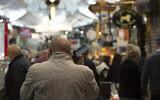 رجل يتحدث بهاتفه المحمول في سوق محانيه يهودا في القدس، 23 ديسمبر، 2020. (Maya Alleruzzo / AP)
