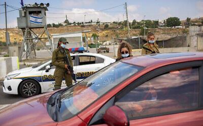 جنود إسرائيليون يتحققون من هويات الفلسطينيين عند حاجز مفرق تفوح بالقرب من مدينة نابلس في الضفة الغربية، 30 يونيو، 2020. (AP Photo / Oded Balilty، File)