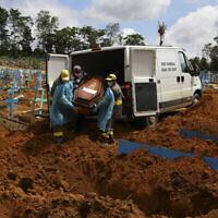 """عمال مقبرة يدفنون ضحية فيروس كورونا في مقبرة """"نوسا سينهورا أباريسيدا"""" في ماناوس  بولاية الأمازون، البرازيل، 6 يناير، 2021. (AP Photo / Edmar Barros)"""