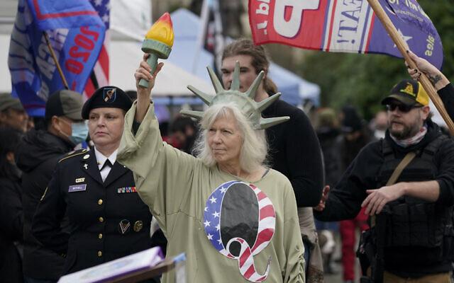 """سيدة ترتدي زي تمثال الحرية مع حرف Q، في إشارة إلى """"كيو آنون""""، بينما يشارك متظاهرون في احتجاج في مبنى الكابيتول في أولمبيا، واشنطن، ضد فرز الأصوات الانتخابية في واشنطن العاصمة، 6 يناير 2021 (Ted S. Warren / AP)"""