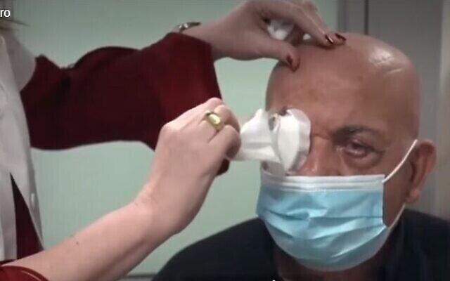 البروفيسور إيريت بهار، مديرة قسم طب وجراحة العيون في مركز رابين الطبي، تزيل الضمادات عن عيني جمال فوراني ، بعد خضوعه لعملية زرع قرنية اصطناعية طورتها شركة CorNeat Vision  (لقطة شاشة Channel 13)