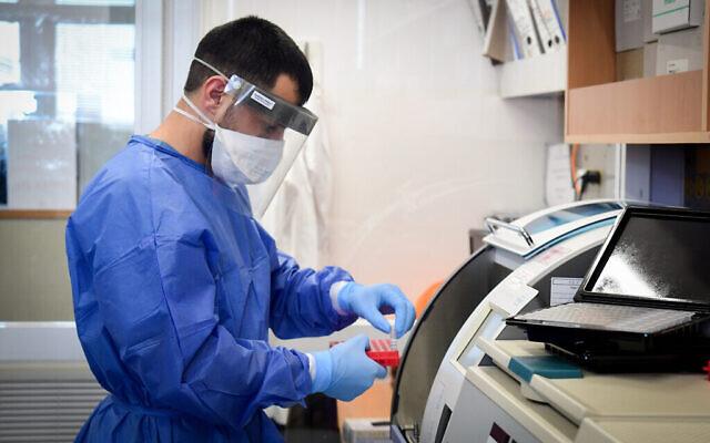 توضيحية - عامل فريق طبي في مستشفى برزيلاي في أشكلون يتعامل مع عينة اختبار كورونا، 29 مارس، 2020. (Flash90)