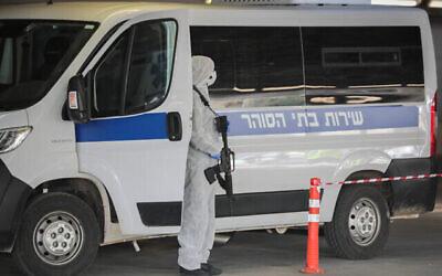 حراس سجن يرتدون ملابس واقية كإجراء وقائي ضد فيروس كورونا، أثناء نقلهم لسجين يشتبه في إصابته بفيروس كورونا في مركز شعاري تسيديك الطبي في القدس، 30 مارس، 2020. (Yossi Zamir / Flash90)