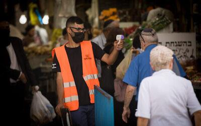 توضيحية: رجل يفحص درجة حرارة متسوق عند مدخل سوق محانيه يهودا في القدس، 18 يونيو، 2020. (Yonatan Sindel / Flash90)