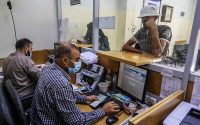 فلسطينيون يتلقون مساعداتهم المالية في اطار المعونات التي قدمتها قطر في مكتب بريد في رفح، جنوب قطاع غزة، 6 أكتوبر، 2020. (Abed Rahim Khatib / Flash90)