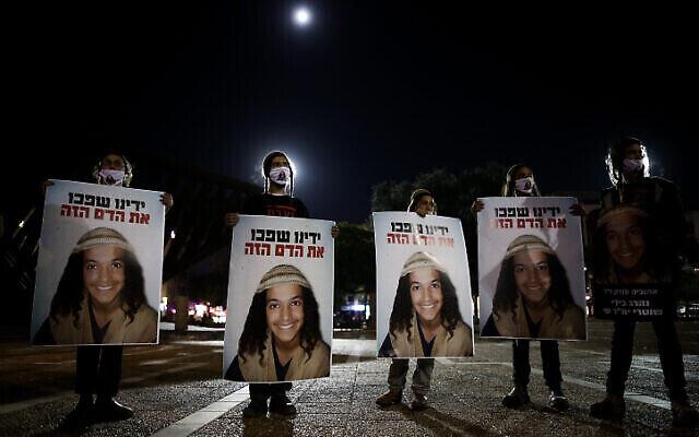 متظاهرون يحملون لافتات تحمل صورة أهوفيا سنداك خلال احتجاج على مقتله في انقلاب مركبته خلال مطاردة شرطية في الأسبوع الماضي، في ميدان رابين بتل أبيب، 29 نوفمبر، 2020. (Miriam Alster/Flash90)