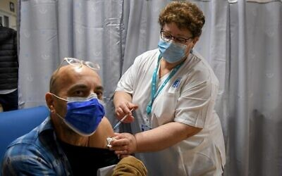 مدرس إسرائيلي يتلقي التطعيم ضد كوفيد-19، في المركز الطبي شمير في بئر يعقوب، 30 ديمسبر، 2020. (Avi Dishi/Flash90)