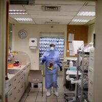 أعضاء طاقم طبي في مستشفى إيخيلوف يرتدون ملابس واقية أثناء عملهم في قسم  كورونا في المستشفى، تل أبيب، 1 يناير 2021. (Tomer Neuberg / Flash90)