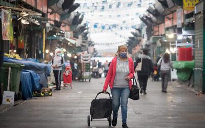 امرأة تسير في سوق هاتكفا في تل أبيب خلال إغلاق عام، 3 يناير، 2021. (Miriam Alster / Flash90)