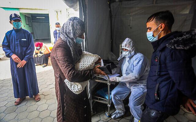 عامل صحي فلسطيني يأخذ عينات لتشخيص فيروس كورونا في مركز صحي في رفح، جنوب قطاع غزة، 5 يناير، 2021. (Abed Rahim Khatib / Flash90)