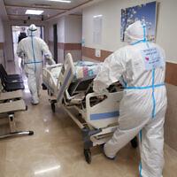 طاقم مستشفى ينقل مريضا جديدا الى قسم كورونا في المركز الطبي زيف في مدينة صفد شمال اسرائيل، 7 يناير 2020. (David Cohen / Flash90)