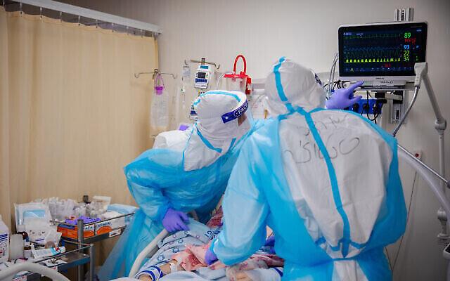 عاملون صحيون في مركز شعاري تسيديك الطبي في القدس ينقلون مرضى إلى جناح فيروس كورونا الجديد في المستشفى، 7 يناير 2021 (Olivier Fitoussi / Flash90)