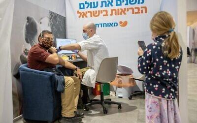 أشخاص يتلقون لقاح كوفيد-19، في مركز تطعيم كوفيد-19 تابع لصندوق المرضى مئوحيدت في القدس، 7 يناير، 2021.(Yonatan Sindel/Flash90)